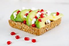 Avokado med Feta, granatäpple på smörgåsen för bröd för solrosfrö Royaltyfri Foto