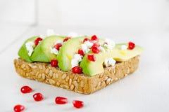 Avokado med Feta, granatäpple på smörgåsen för bröd för solrosfrö Arkivbilder
