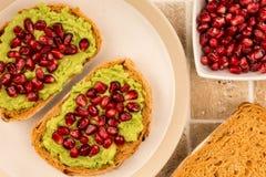 Avokado- och granatäpplefrö öppnar framsidasmörgåsen på Mediterranea Royaltyfri Bild