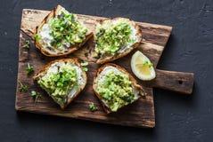 Avokado- och ricottarostat bröd med microen gör grön på en skärbräda, på en mörk bakgrund, den bästa sikten Sunt ätabegrepp för b arkivbild
