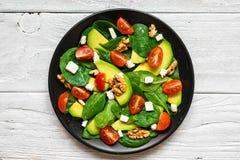 Avokado- och spenatsallad med tomater körsbär, fetaost och valnötter i en platta på den lantliga trätabellen Top beskådar royaltyfri bild