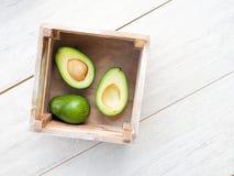 Avokado på den gamla trätabellen Halfs på träbunken Bär frukt det sunda matbegreppet avokado i en träask arkivfoto