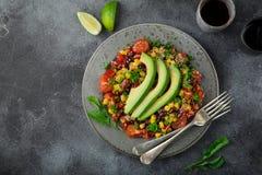 Avokado-, quinoa-, böna-, havre- och spansk pepparsallad, grå backgrou arkivfoto