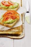 Avokadokräm med rostade bröd och tomater Royaltyfria Bilder