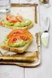 Avokadokräm med rostade bröd och tomater Royaltyfri Bild