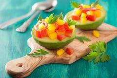 Avokadon som är välfyllda med tomatpepparsallad arkivfoto