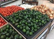 Avokadon, tomater och lökar som är till salu i supermarketlivsmedelsbutik royaltyfri fotografi