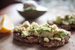 Avokadorostat bröd med citronen och spiskummin på den Wood tabellen arkivbild