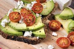 Avokadorostat bröd med körsbärsröda tomater och fetaost Royaltyfri Foto
