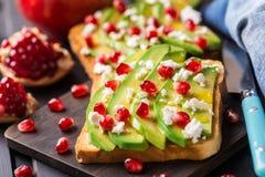 Avokadosmörgås med feta och granatäpplet Arkivbild
