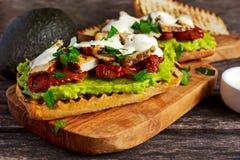 Avokadosmörgås med solsken torkade tomater, grillat griskött och såsörter Royaltyfri Fotografi