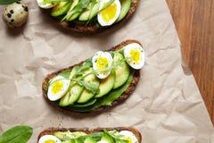 Avokadosmörgåsrostat bröd på kavring som göras med nya skivade avokadon med spenat-, guacamole-, arugula- och vaktelägg royaltyfri fotografi
