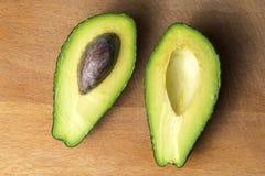 Avokadosnitt in i 2 stycken på kökbrädet royaltyfria foton