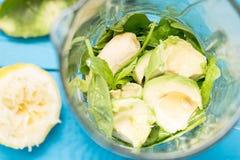 Avokadot, bananen, citronjuice, spenat och mandeln mjölkar i blandare, absolut fantastisk smaklig grön avokadoskaka eller Smoothi Royaltyfria Bilder