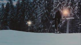 avond aangestoken skisleep Skiërs en snowboarders stock videobeelden