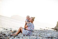 Avond, overzees strand De zoon zit op zijn moeder` s overlapping en eet fruit en bessen Stock Foto's