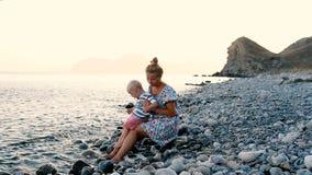 Avond, overzees strand De zoon zit op zijn moeder` s overlapping en eet fruit en bessen stock video