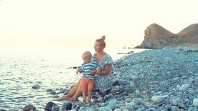 Avond, overzees strand De zoon zit op zijn moeder` s overlapping en eet fruit en bessen stock footage