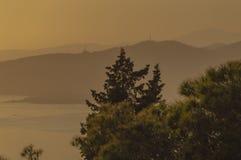 Avonden die op het overzees en de berg met gouden licht letten royalty-vrije stock foto's