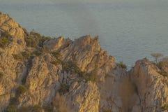 Avonden die op het overzees en de berg met gouden licht letten stock afbeelding