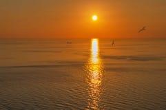 Avonden die op het overzees en de berg met gouden licht letten stock foto's