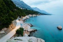 Avondkustlijn met rotsen, bomen en bergen in Brela, Kroatië bij het Adriatische Overzees Stock Foto's