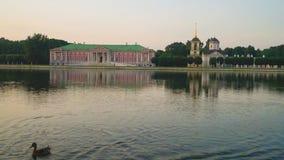 Avondmening door de vijver op het paleis en kerk met klokketoren in museum-landgoed Kuskovo, Moskou stock video