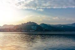 Avondmening van de stad van het meer Mening van de de stadswaterkant en bergen stock foto