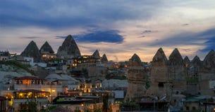 Avondmening van het dorp van Goreme in Cappadocia op de achtergrond van het natuurlijke terrein en de avondhemel royalty-vrije stock fotografie