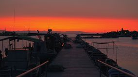 Avondscène van kade Pijler, boten en oranje hemel stock videobeelden