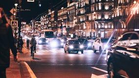 Avondstad met Auto en Mensenverkeer Stock Afbeeldingen