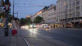 Avondstad, partij van auto's met het branden koplamp het drijven op weg voorbij huizen en voetgangers stock videobeelden