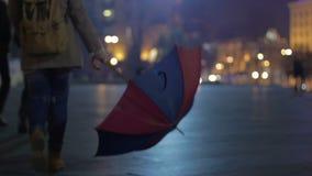 Avondtijd, vrouw met geopende paraplu die onderaan de straat, droefheid lopen stock footage