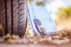 Avonturenreis: sluit van autoband, zonnebril en wegenkaart stock foto's