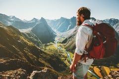 Avontuur bij de bergenmens met rode rugzak alleen op klip stock fotografie