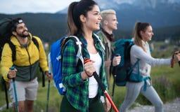 Avontuur, reis, toerisme, stijging en mensenconcept - groep glimlachende vrienden met rugzakken en kaart in openlucht stock foto