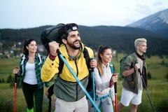 Avontuur, reis, toerisme, stijging en mensenconcept - groep glimlachende vrienden met rugzakken en kaart in openlucht stock afbeelding