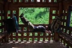 Avontuur, toerisme, die de zomer van tijd genieten - de jonge wandelaar van de toeristenmens met rugzak plakt het rusten op bank  Royalty-vrije Stock Foto