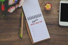 Avril dupe la liste des textes de jour sur la note de livre avec la tasse photographie stock