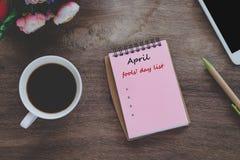 Avril dupe la liste des textes de jour sur la note de livre avec la tasse photo libre de droits