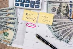 15 avril, jour d'impôts sur le calendrier avec le stylo de marqueur rouge avec le billet de banque du dollar, stylo Image stock