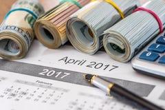 15 avril, jour d'impôts sur le calendrier avec le stylo de marqueur rouge avec le billet de banque du dollar, stylo Images stock