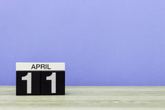 11 avril Jour 11 de mois, calendrier sur la table en bois et fond pourpre Printemps, l'espace vide pour le texte Photographie stock