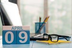 9 avril Jour 9 de mois, calendrier sur le fond de local commercial, lieu de travail avec l'ordinateur portable et verres Printemp Photos libres de droits