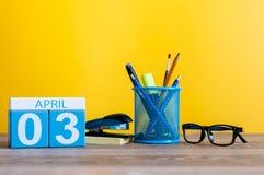 3 avril Jour 3 de mois d'avril, calendrier sur la table avec le fond jaune et bureau ou fournitures scolaires Le printemps… a mon Photos stock