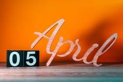 5 avril Jour 5 du mois, calendrier en bois quotidien sur la table avec le fond orange Concept de printemps Image stock