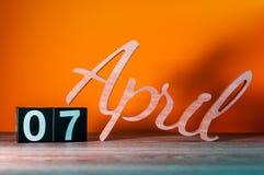7 avril Jour 7 du mois, calendrier en bois quotidien sur la table avec le fond orange Concept de printemps Images libres de droits