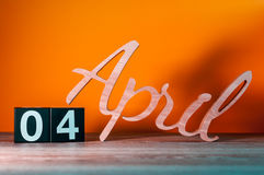 4 avril Jour 4 du mois, calendrier en bois quotidien sur la table avec le fond orange Concept de printemps Photographie stock libre de droits