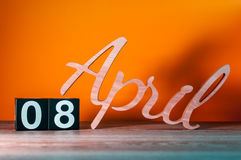 8 avril Jour 8 du mois, calendrier en bois quotidien sur la table avec le fond orange Concept de printemps Images stock