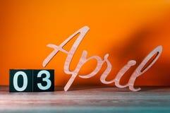 3 avril Jour 3 du mois, calendrier en bois quotidien sur la table avec le fond orange Concept de printemps Images stock